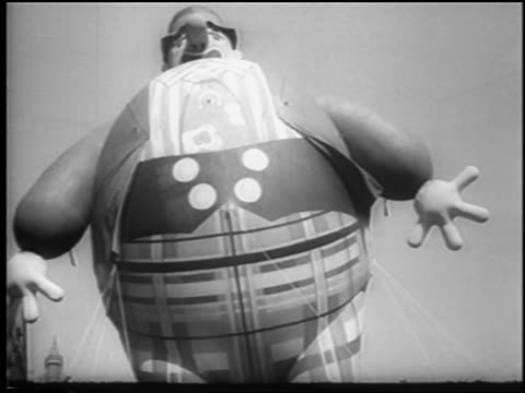 B/W 1945 low angle giant clown balloon in air at Macy's Thanksgiving Day parade / NYC / newsreel