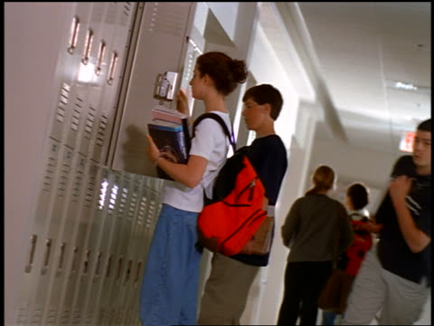 stockvideo's en b-roll-footage met canted low angle girl removing books from locker / students walking in high school hallway - lockerkast