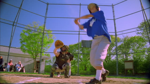 low angle girl swinging bat and hitting baseball / running - baseballmannschaft stock-videos und b-roll-filmmaterial