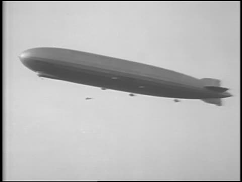 B/W 1929 low angle Graf Zeppelin flying in sky / small airplane flying underneath / newsreel