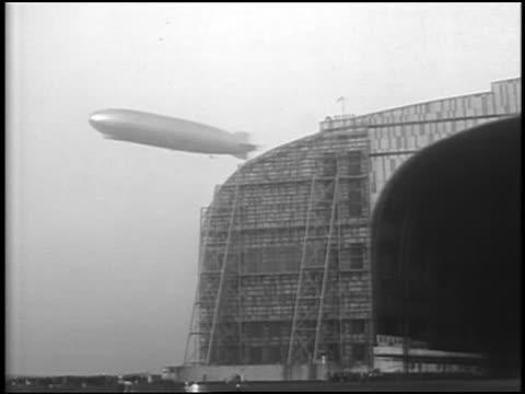 B/W 1929 low angle PAN Graf Zeppelin flying over hangar / Lakehurst, NJ / newsreel