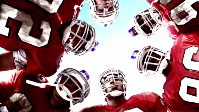 vidéos et rushes de overexposed low angle ms group of football players in huddle listen to quarterback, clap hands + walk away - serré