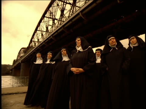 low angle group of nuns standing under bridge bobbing heads to beat of music / prague - nun stock videos & royalty-free footage