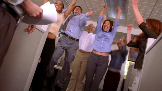 low angle group of office workers celebrating and cheering after hearing good news from manager - high five stock videos & royalty-free footage