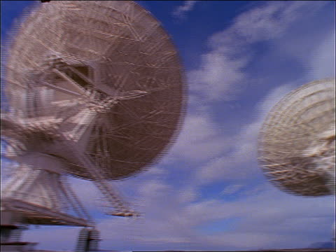 stockvideo's en b-roll-footage met low angle pan group of radio telescopes/satellite dishes / blue sky + white clouds above - radiozender
