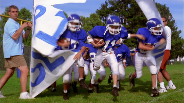 Low angle group of young boys wearing blue football jerseys running and breaking through banner