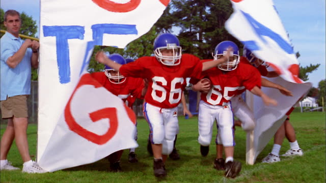 Low angle group of young boys wearing red football jerseys running and breaking through banner