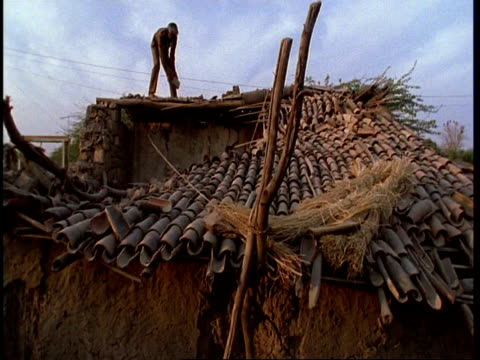 ms low angle, gujarat, indian man on roof of ruined house, after earthquake, gujarat, india - グジャラート州点の映像素材/bロール