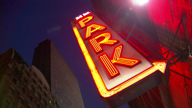 low angle hand,held pan,right , an arrow flashes on a neon sign for a 24,hour parking garage. / new york city, new york, usa - schild stock-videos und b-roll-filmmaterial