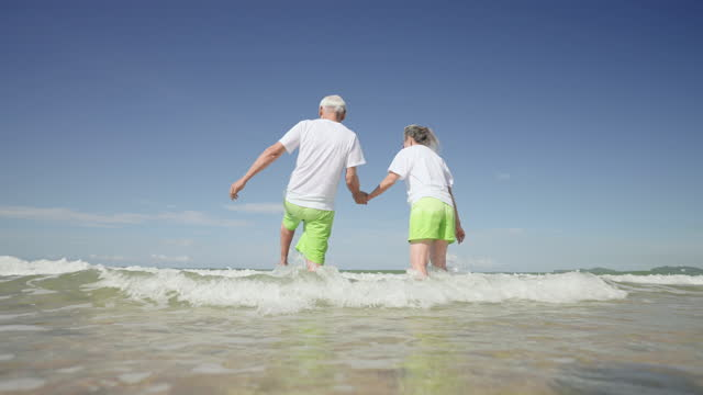 low angle handheld slow-motion view: mature couple playing seawater with feeling positive emotion, excited in  the same swimming couple cloth at the beach, concept of  retirement senior adult in holiday summer - swimming shorts stock videos & royalty-free footage