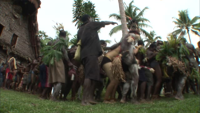 low angle hand-held - tribesmen in papua new guinea dance together in a traditional ceremony. / papua new guinea - papua stock videos and b-roll footage