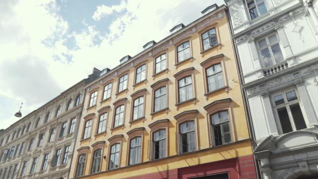 låg vinkel handhållen utsikt medan promenader i marknadsgatorna för att se gamla byggnaden längs det i köpenhamn, danmark - lägenhet bildbanksvideor och videomaterial från bakom kulisserna