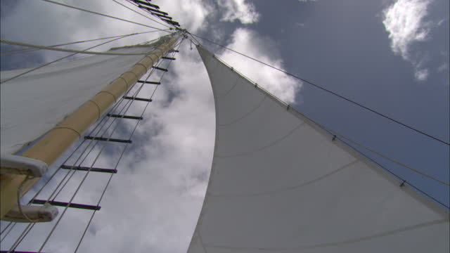 Low Angle hand-held - Wind rustles a sail as it is raised in a sailboat / Great Barrier Reef, Australia