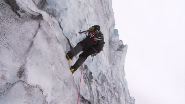 """low angle hand-held-an ice climber uses pickaxes to ascend a rockface. / juneau, alaska, usa"" - カラビナ点の映像素材/bロール"