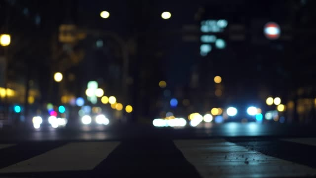 Low angle high contrast 4k video on busy night street with cars.