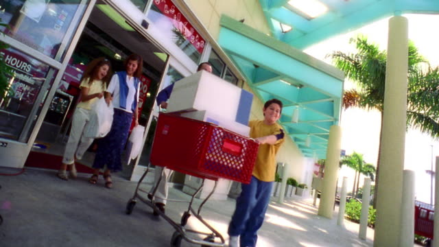 canted low angle hispanic family exiting store with full shopping cart + shopping bags / florida - handwagen stock-videos und b-roll-filmmaterial