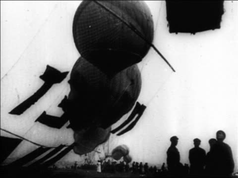 B/W 1927 low angle hot air balloon trailing huge banner with Russian words taking off from ground / Russia