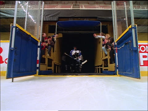 low angle ice hockey team coming out onto ice / fans applauding them in stands