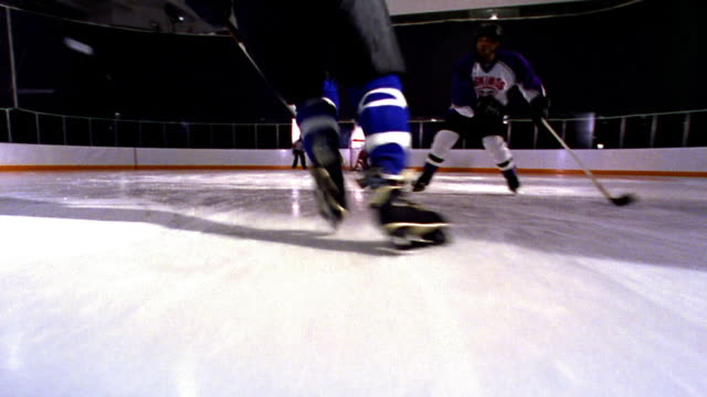 low angle ice skating point of view following male hockey player skating with puck past players toward goal + scoring