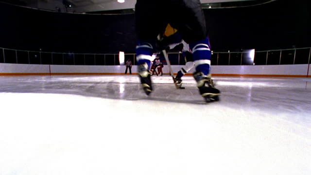 low angle ice skating point of view following male hockey player skating with puck toward goal + shooting/ goalie saves - low angle view stock videos & royalty-free footage