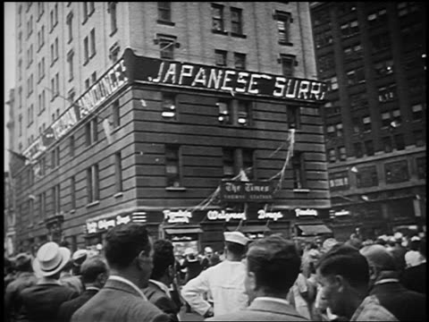 B/W 1945 low angle Japanese Surrender on ticker board in Times Square / crowd confetti in foreground / NYC