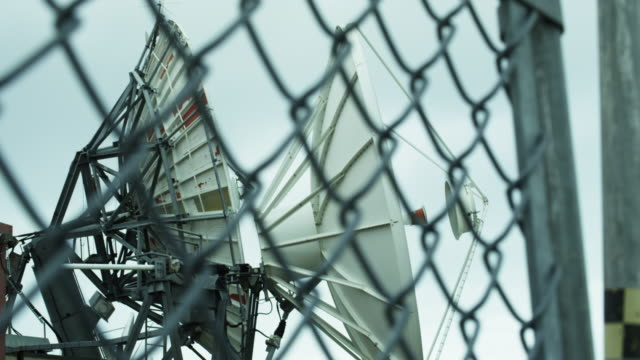 vídeos de stock, filmes e b-roll de low angle, large satellites behind fence - onda radiofônica