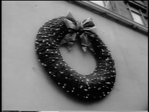 stockvideo's en b-roll-footage met b/w 1963 low angle lighted wreath handing on building / nyc / newsreel - krans