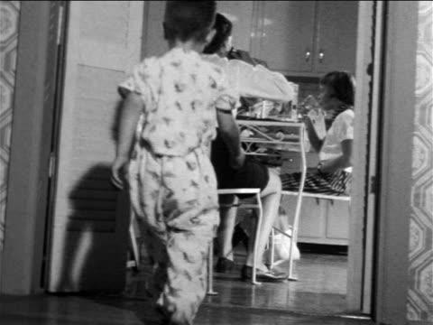 vídeos y material grabado en eventos de stock de b/w 1957 low angle little boy wearing pajamas joining family in kitchen at breakfast table / educational - 1957