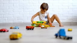 Low angle Little caucasian boy playing with cars on the floor, 4k