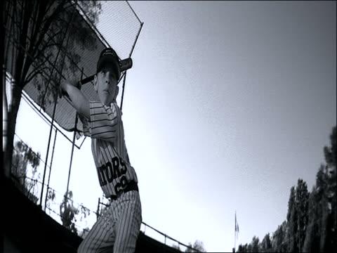B/W low angle Little League baseball player in uniform swinging bat + running