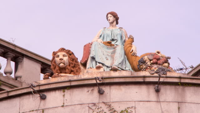 low angle lockdown shot of animal and human statue on structure in city against clear sky - aberdeen, scotland - female likeness stock videos & royalty-free footage