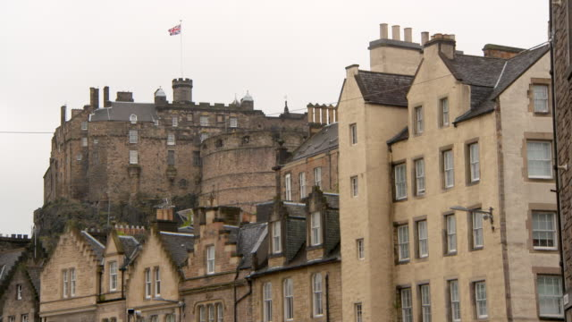 low angle lockdown shot of british flag on historic castle in city against sky - edinburgh, scotland - stone object stock videos & royalty-free footage