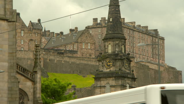 low angle lockdown shot of clock tower against buildings at famous historic castle in city - edinburgh, scotland - pinnacle stock videos & royalty-free footage