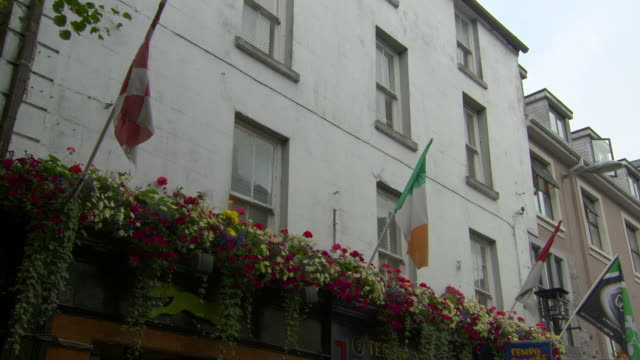 low angle lockdown shot of flags and flowers on building in city - galway, ireland - angle stock videos & royalty-free footage