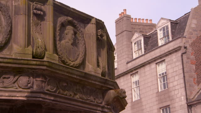 low angle lockdown shot of ornate structure with carvings against building on city - aberdeen, scotland - male likeness stock videos & royalty-free footage