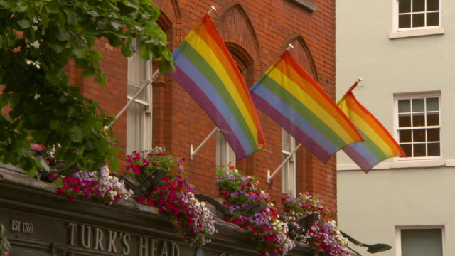 low angle lockdown shot of rainbow flags on building in city - dublin, ireland - pride stock videos & royalty-free footage