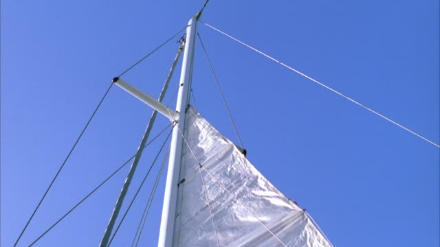 low angle locked off shot of a sail being hoisted up a mast - hoisting stock videos & royalty-free footage