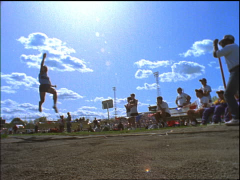 low angle long jumper lands in sandpit - salto in lungo video stock e b–roll