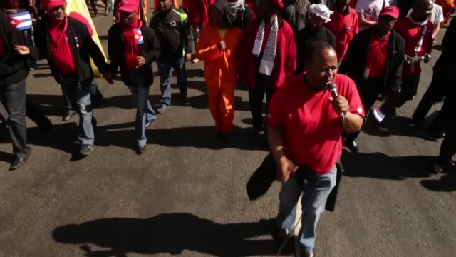 Low angle long shot A man sings a song of support for former South African President Nelson Mandela as he leads antiAmerican demonstrators who are...