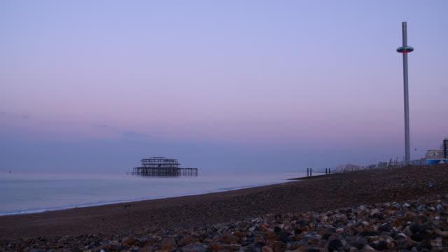 Low angle long shot across Brighton Beach at dawn.