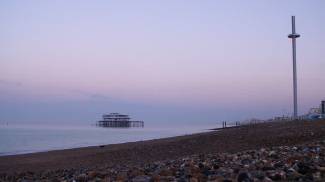 Low angle long shot across Brighton Beach at dawn.