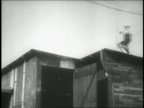 B/W 1914 low angle long shot boxer jumping + running on roof / feature