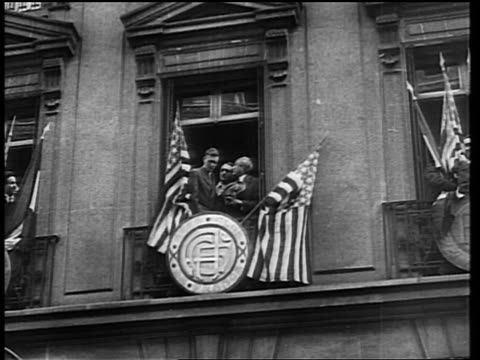 B/W 1927 low angle long shot Charles Lindbergh holding US flag standing on balcony with French officials / Paris