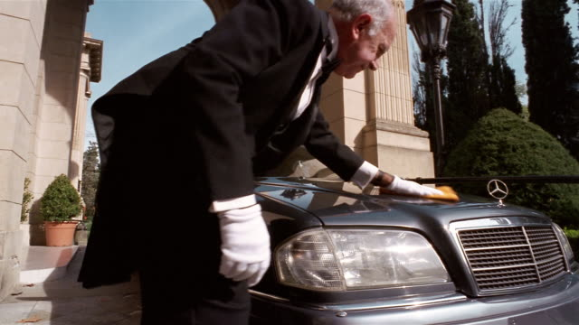 Low angle long shot chauffeur polishing hood of limousine
