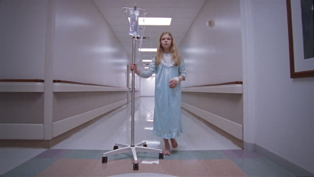 low angle long shot dolly shot girl walking down hospital hallway rolling her iv drip - korridor stock-videos und b-roll-filmmaterial