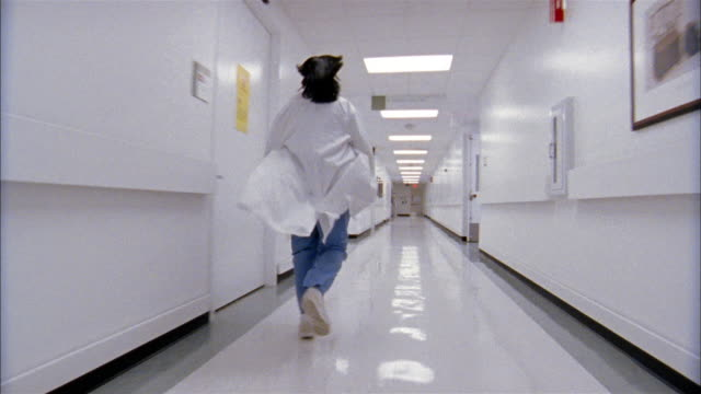 Low angle long shot dolly shot slow motion doctor wearing scrubs running down hospital hallway / turning corner