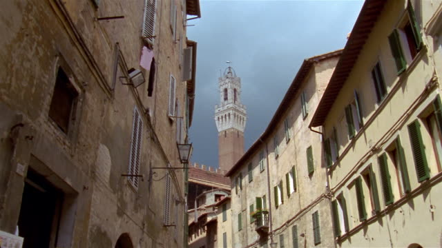 low angle long shot exterior of buildings on narrow street with torre del mangia in background / siena, tuscany, italy - torre del mangia stock videos and b-roll footage