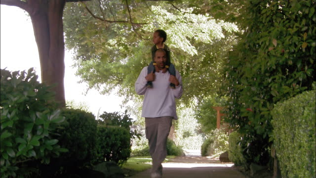 Low angle long shot father carrying young son on shoulders as he walks down the sidewalk