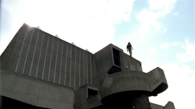 low angle long shot freerunner standing on roof / jumping off ledge / london - roof stock videos & royalty-free footage