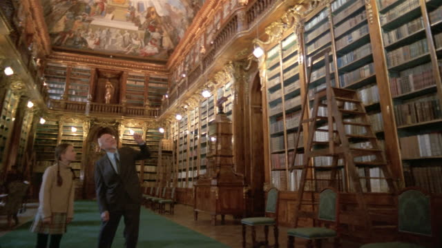 Low angle long shot girl and grandfather talking in Philosophical Hall library at Strahov Monastery / Prague